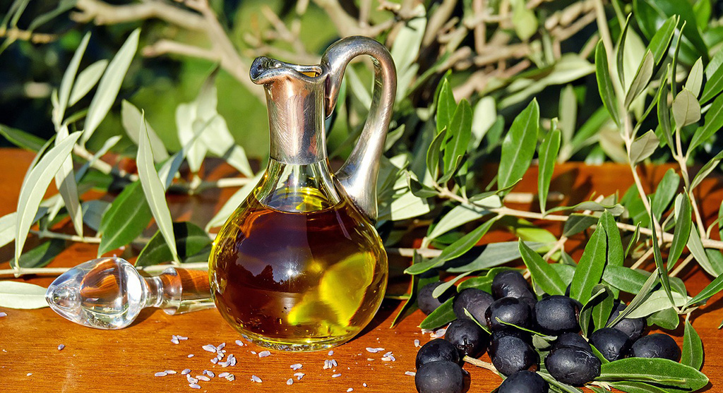 Olive and oil in a glass jug next to a tree